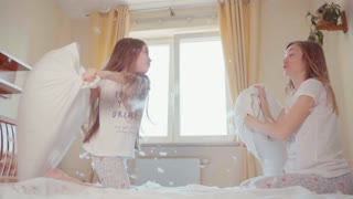 Fighting pillows on the bed. Mother and daughter fighting on the bed in sunny bedroom. Among the fluff and feathers. Child win. Slowmotion