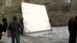 Film Crew Moves Reflector Near Primping Actress