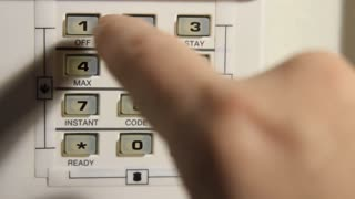 Finger Pushing Buttons On Home Security System
