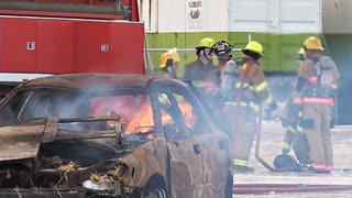 Firefighters By Flaming Car