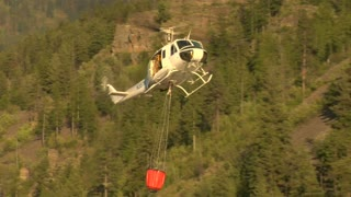 Firefighting Helicopter Collects Water From River