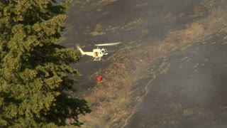 Firefighting Helicopter Flies By Charred Hillside