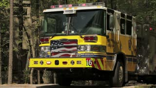 flashing fire truck in woods with firefighters
