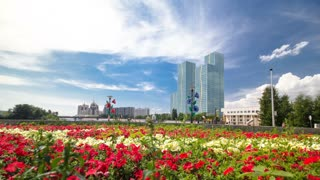 Flowerbed with red and yellow flowers on embankment near river timelapse hyperlapse on the background of blue sky with clouds and green towers. Astana, Kazakhstan. Sunny day. 4K