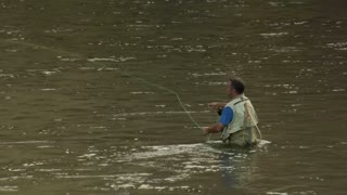 Fly Fisherman In Hip Waders In River