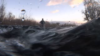 Fly Fisherman Shot From Underwater Camera Near Waves