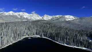 Flying backwards over Lost Lake in Colorado Rocky Mountains in winter with snow