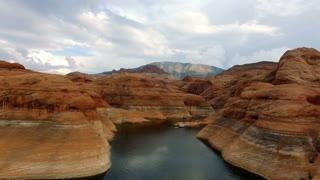 Flying backwards through canyons in Lake Powell on a cloudy day