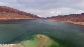 Flying backwards to reveal a houseboat in Lake Powell Utah