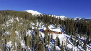 Flying backwards to reveal a snow covered winter cabin in Colorado Rocky Mountains