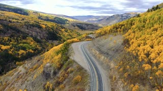Flying backwards to reveal a winding road through Colorado Rocky Mountains in autumn