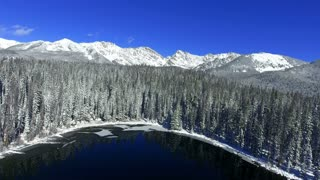 Flying backwards to reveal snow covered pine trees and deep blue mountain lake in Colorado Rockies