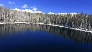 Flying close to the water over a snowy mountain lake in the winter