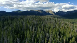 Flying left over tree tops to reveal Lost Lake in Vail Colorado Rocky Mountains