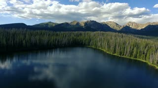 Flying low over Lost Lake in Vail Colorado with pine trees and Rocky Mountains in background