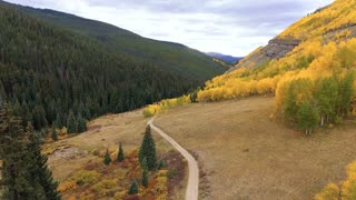 Flying over a dirt road in Colorado Rocky Mountains in autumn