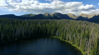 Flying over a lake and into pine trees with blue sky clouds and Rockies in background