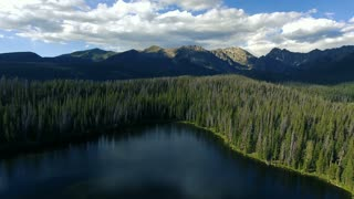 Flying over a lake in the Colorado Rocky Mountain Rockies on sunny day with clouds