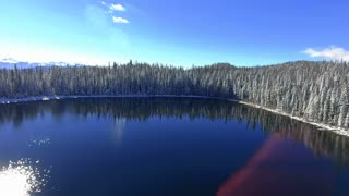 Flying over a snow covered lake in winter with snowy pine trees