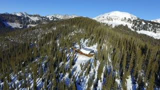 Flying over a snow covered winter cabin in the woods panning down aerial shot