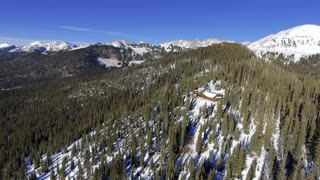 Flying over a snowy cozy cabin in the woods of Colorado Rocky Mountains