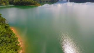 Flying over an emerald lake backwards