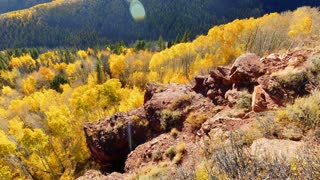 Flying over red rocks and cliffs with Aspen trees and fall foliage in autumn