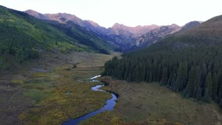 Flying over snaking river to Piney Lake in Rocky Mountains at sunset