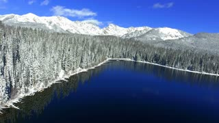 Flying over winter lake in Rocky Mountains with snow