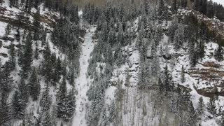Flying through snow covered forest towards ice waterfall