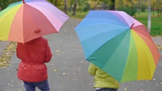 Following shot of little girls with big umbrellas with rainbow print walking in park on chilly autumn day