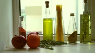 Food ingredients near kitchen window. Cooking oil and kitchen herbs. Extra virgin olive oil in glass bottle. Rosemary herb and garnet fruit. Raw spaghetti. Cooking ingredients