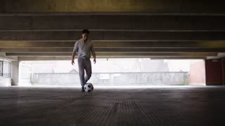 Football player doing kick ups in an urban city environment, in slow motion
