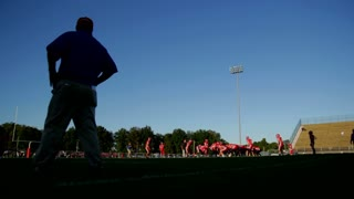 Football players practice a play as their coach watches them from the sideline.