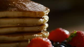 Fork taking a slice of stacked buttermilk pancakes drenched in maple syrup, in slow motion