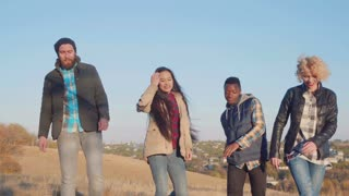 Four different ethnicity friends hanging out at rural areas, showing lipstick sign, laughing and dancing