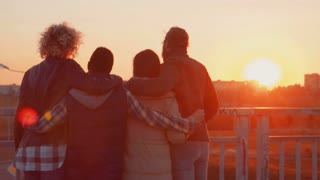 Four different ethnicity friends hanging out on bridge at sunset