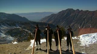 Four German Men Blow Long Horns On Mountain