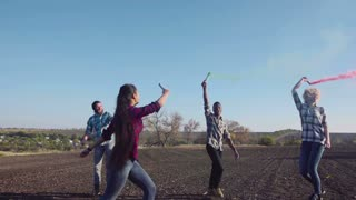 Four happy young multi racial friends dancing in field with colored smoke grenades