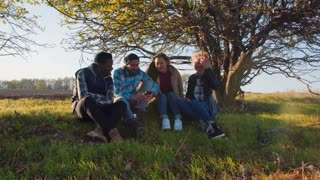 Four multiracial friends sitting on ground near beautiful tree and sharing photo images on smart phone. Round camera, backlit