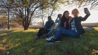 Four multiracial friends sitting on ground near beautiful tree opposite the sun doing selfie and sharing photo images on smart phone. Round camera, backlit