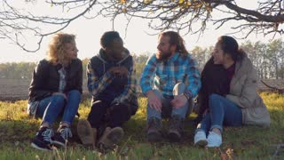 Four multiracial friends sitting on ground talking and laugh. round camera, backlit