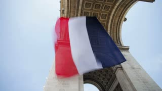 French flag flying under the Arc de Triomphe in Paris, France - T/Lapse