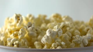 Fresh popcorn falling into paper box. Cinema, overflow or fast food concepts. Super slow motion dolly shot