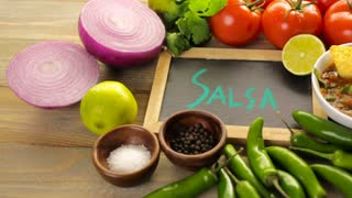 Fresh salsa in white bowl with ingredients.