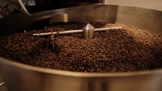 Freshly baked coffee beans mixing in cooling pot of roasting machine before sorting and packing. Side view, looped video