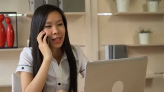 Friendly business woman using app on smartphone and talk with smile on her face. Happy female phones at the working place her boyfriend. Attractive ethnic model with long black hair wearing in formal