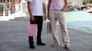 Friends stand and talk while holding shopping bags