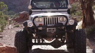 Front of white jeep driving over rock