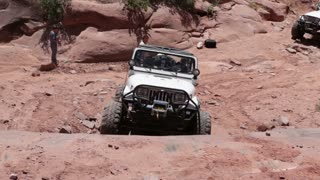 Front of white jeep driving up canyon
